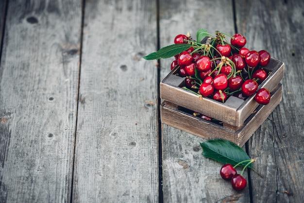 Cerejas com folhas em caixa de madeira vintage na mesa de madeira rústica. copie o espaço.