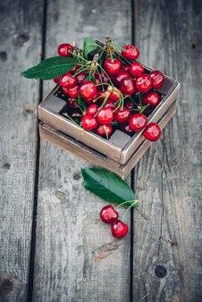 Cerejas com folhas em caixa de madeira vintage na mesa de madeira rústica.