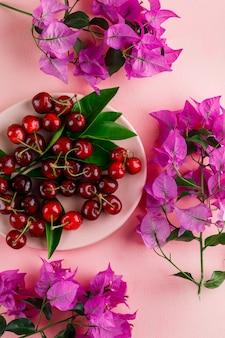 Cerejas com folhas, galhos de flores em um prato na superfície rosa