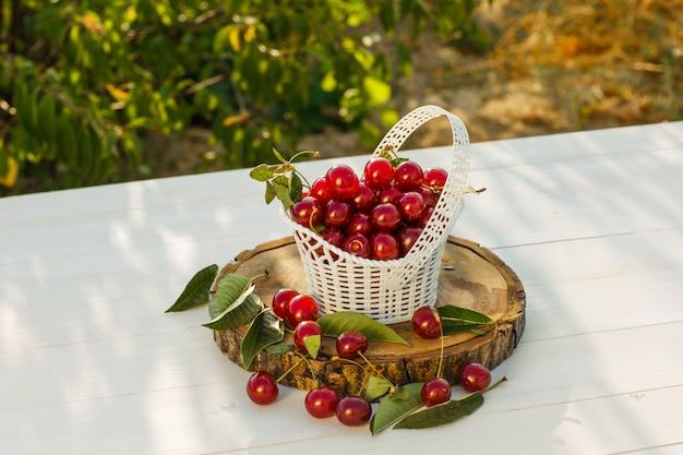 Cerejas com folhas, tábua em uma cesta no fundo de madeira e jardim, vista de alto ângulo.