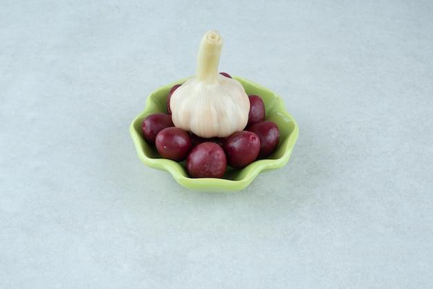Cerejas cornel em conserva em uma tigela com alho fresco.