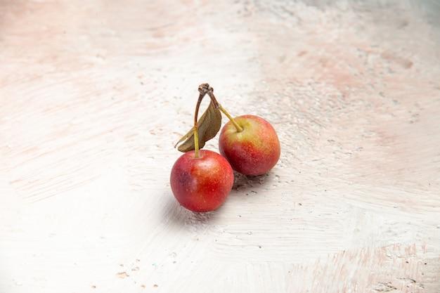Cerejas de cima para cima, cerejas vermelhas e amarelas na mesa rosa-branco-cinza