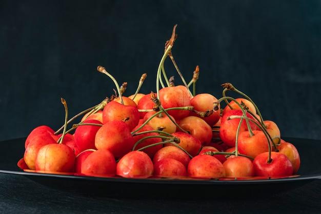 Cerejas-de-rosa na bandeja na vista lateral de fundo preto. cerejas maduras e suculentas. bagas sazonais. fechar-se