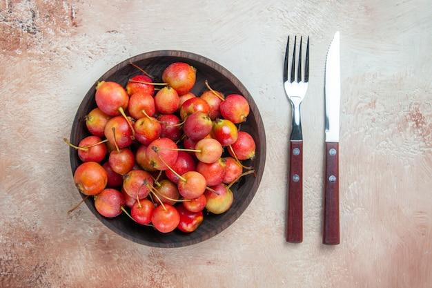 Cerejas de vista de cima em close-up as cerejas apetitosas na faca de garfo tigela sobre a mesa
