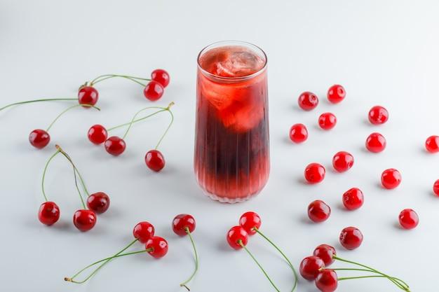 Cerejas dispersas com bebida gelada, vista de alto ângulo.