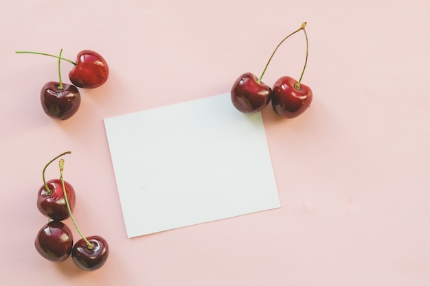 Cerejas doces vermelhas maduras com cartão branco vazio. estilo leigo plano. dieta colorida e conceito de comida saudável.