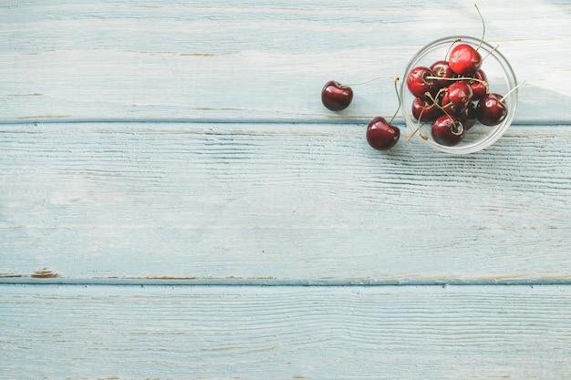 Cerejas doces vermelhas maduras no fundo de madeira azul. lay plana. dieta colorida e conceito de comida saudável.