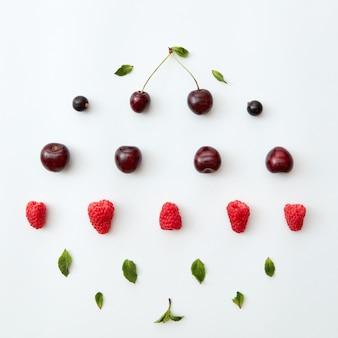 Cerejas e framboesas maduras, groselhas com folhas de hortelã em um fundo branco. padrão de comida criativa