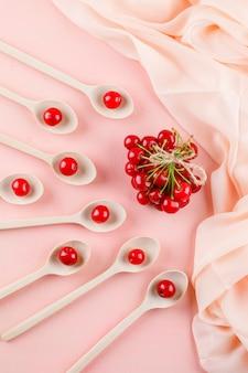 Cerejas em colheres de pau, vista superior no espaço rosa e têxtil