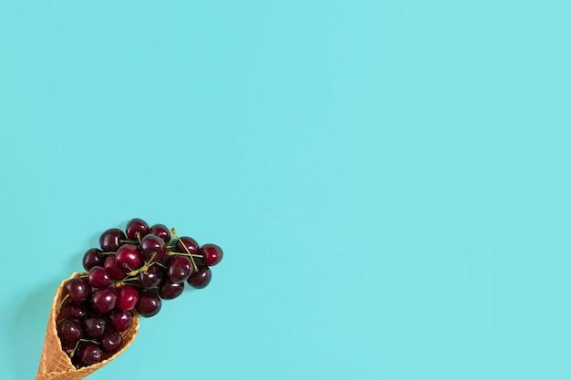 Cerejas em cone waffle na vista superior do fundo azul