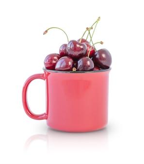 Cerejas em copo vermelho isoladas no fundo branco