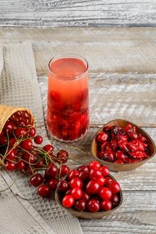 Cerejas em tigelas e cesta com bebida, geléia de alto ângulo vista na toalha de madeira e cozinha
