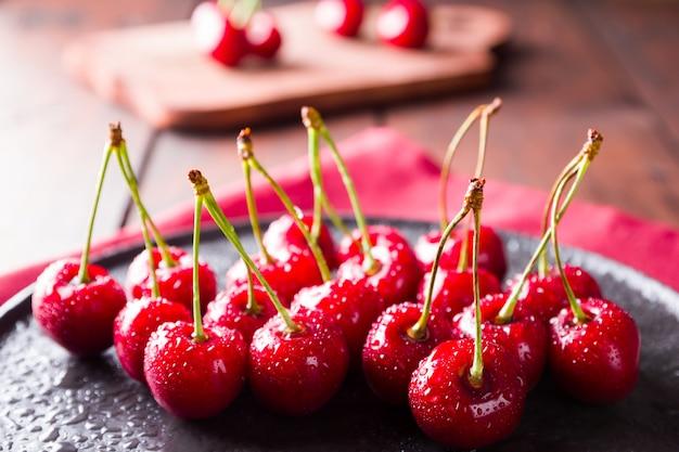 Cerejas em um prato preto. cerejas em uma placa de madeira. bagas vermelhas em gotas de água em um guardanapo vermelho. estilo rústico. copyspace