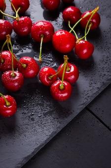 Cerejas em uma placa de ardósia. bagas vermelhas em gotas de água em quadros pretos. comida saudável. vista do topo. copyspace