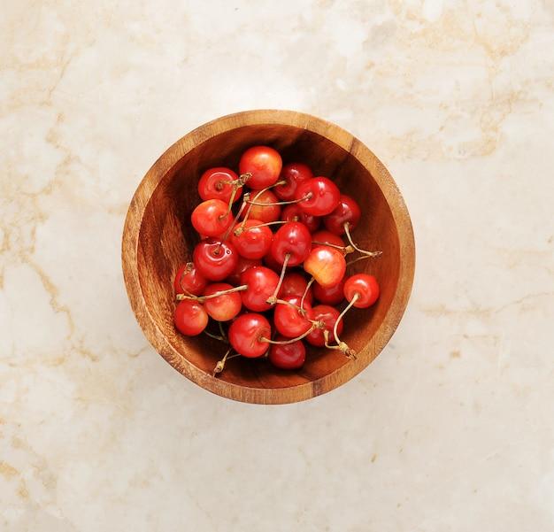 Cerejas em uma tigela de madeira em mármore