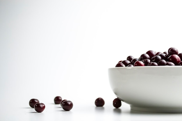 Cerejas em uma xícara branca em um fundo branco e ao lado da xícara cerejas espalhadas