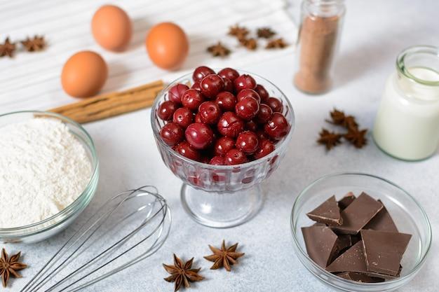 Cerejas enlatadas em uma tigela de vidro e os ingredientes para um bolo doce são preparados na mesa