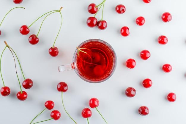 Cerejas espalhadas com chá, plana leigos.