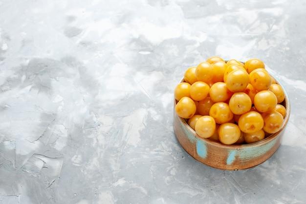 Cerejas frescas amarelas dentro de uma tigela marrom em uma mesa cinza claro, doce de frutas frescas