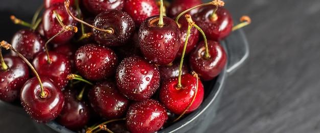 Cerejas frescas com água cai na tigela na mesa de pedra escura.