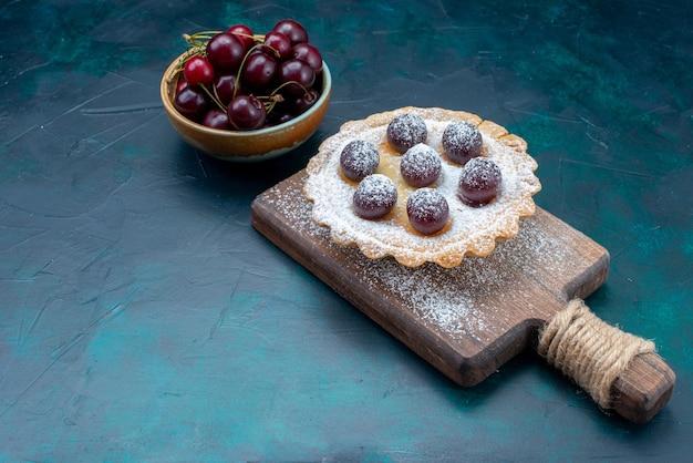 Cerejas frescas com bolo de cereja em azul escuro