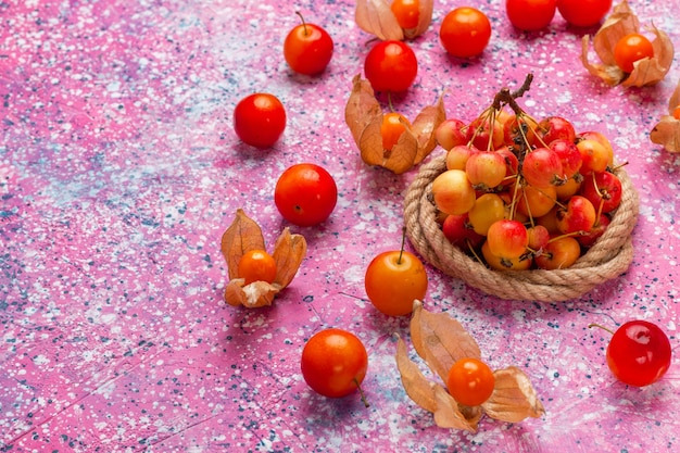 Cerejas frescas de vista frontal com ameixas na mesa rosa claro.