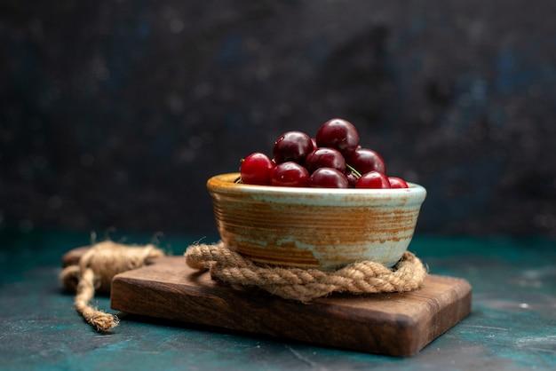 Cerejas frescas dentro da tigela em azul escuro