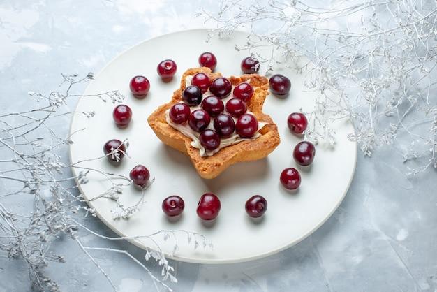 Cerejas frescas dentro do prato com bolo cremoso em forma de estrela em cinza