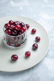 Cerejas frescas dentro do prato em uma mesa branca clara, vitamina de frutas azedas no verão