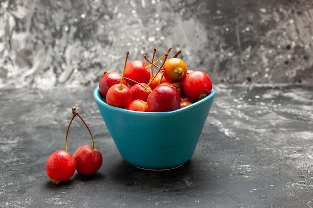 Cerejas frescas dentro e fora de uma cesta azul