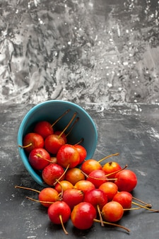 Cerejas frescas derramadas da cesta azul