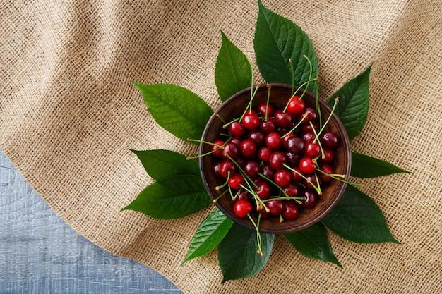Cerejas frescas doces com folhas em pano de saco