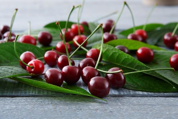 Cerejas frescas doces com folhas verdes