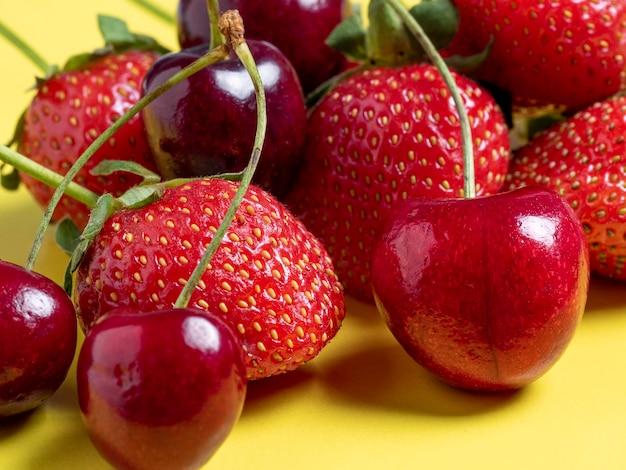 Cerejas frescas e suculentas e morangos em um fundo amarelo brilhante. comida saudável, vegetarianismo, close-up.