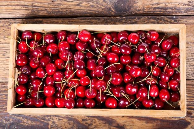 Cerejas frescas em caixa de madeira sobre a mesa