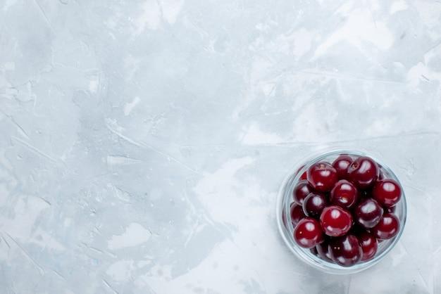 Cerejas frescas em copo de vidro branco claro