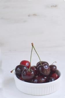 Cerejas frescas em tigela de porcelana branca perda de peso alimentação saudável frutas e bagas de verão colheita de frutas orgânicas