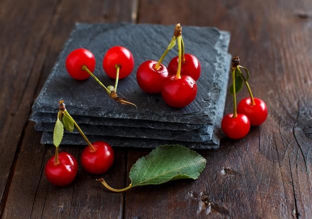 Cerejas frescas em tigelas sobre uma mesa de madeira
