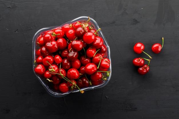 Cerejas frescas em um prato de vidro deitado em uma mesa de gesso preto