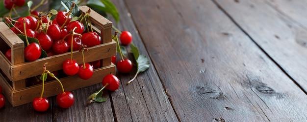Cerejas frescas em uma caixa sobre uma mesa de madeira