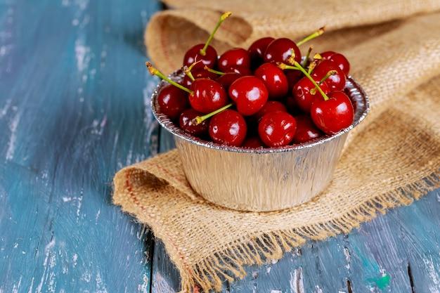 Cerejas frescas em uma caneca de metal antiga. cerejas frescas metal caneca na velha mesa de madeira.