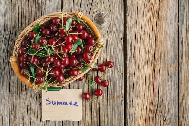 Cerejas frescas em uma cesta com tag e texto de verão