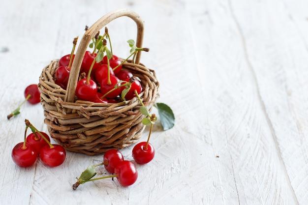 Cerejas frescas em uma cesta sobre uma mesa de madeira