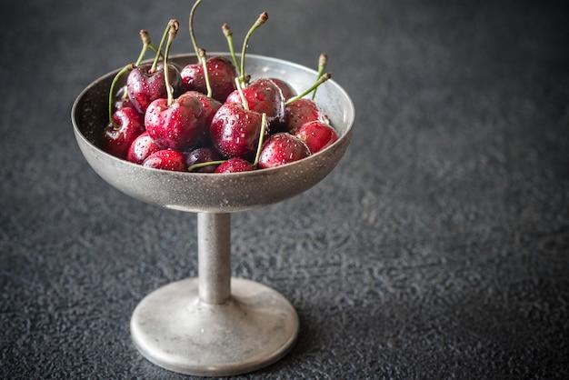 Cerejas frescas em vaso de prata vintage