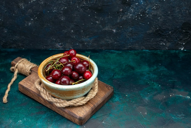 Cerejas frescas maduras e suculentas no escuro