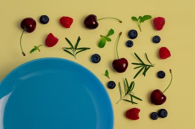 Cerejas frescas, mirtilos, framboesas, hortelã e alecrim folheiam na vista superior com placa azul e fundo de cor amarelo pastel.