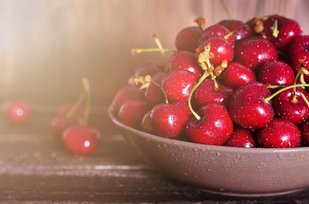 Cerejas frescas na placa no fundo escuro de madeira com espaço de cópia. verão ensolarado e conceito de colheita. macro cereja. vegan, vegetariana, comida crua