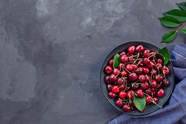 Cerejas frescas orgânicas em uma tigela sobre concreto cinza.