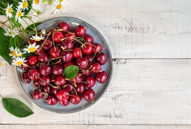 Cerejas frescas orgânicas no prato na mesa de madeira branca. vista do topo.
