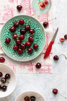 Cerejas frescas rasgadas em um prato verde flatlay